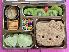 Hello Kitty sandwich, cucumbers, kiwi, wheat crackers, hummus, candy coated sunflower kernels.