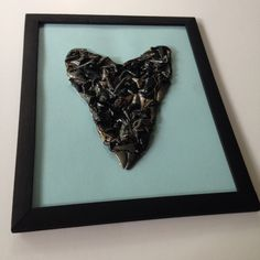 "Shark tooth art!!  Large ""megalodon"" shark tooth made of shark teeth on light blue card stock paper in black frame!  Available for purchase at www.etsy.com/shop/TwoGirlsandaBoat"