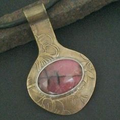The+beautiful+rhodonite+stone+is+set+in+a+fine+silver+bezel,+against+a+bronze+back+plate.++The+bronze+has+been+etched+and+oxidized+to+bring+out+the+details.++The+back+side+is+decorated+with+a+small+flower+cut+out+where+the+stone+shows+through.++It+hangs+from+a+black+leather+cord+that+is+finished+...