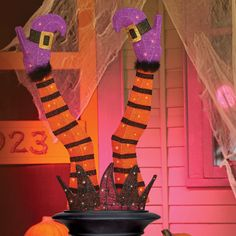 """Um, she didn't """"stick"""" the landing…This poor Witch missed her mark and landed upside down in an urn! Stake this whimsical Halloween decoration in an urn or a large pot and sit her on the porch so she can greet your guests as they arrive."""