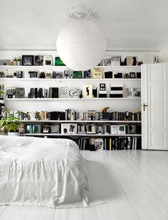 all white bedroom interior w/ shelves and black books (touches of green and gold accent pieces)