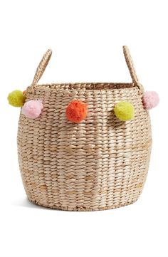 Colorful pompoms add a fanciful touch to this decorative woven basket that enhances the vintage charm of any space.