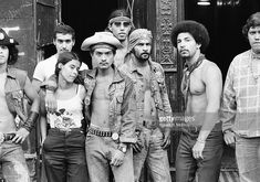 Group portrait of members of Bronz street gang the Dragons as they stand toegther on a sidewalk, New York, New York, 1975.