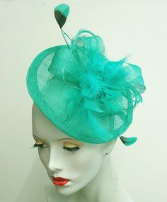 This jade green fascinator has been made by me using blocked, wired sinamay. The saucer base measures 9 inches in diameter. The top has rolls and loops of bias cut sinamay and a profusion of toning goose, biot and coque feathers. The hat is mounted on a sinamay covered metal headband and can be worn to either side of the head. One size. Handmade in England and ready to ship  Any questions please ask I am always happy to help