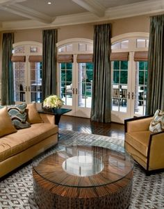 Soft grey/blue stationary drapery panels with neutral Roman shades over the French doors.