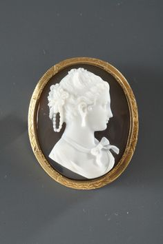 Cameo composedof two layers of agate featuringthe profile of a young woman. She is wearing a ribbon around her neck, earrings, and flowers and pearls in her hair. Her hair and face are very intri...