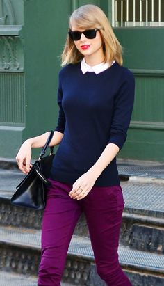 Taylor Swift wears a navy sweater with a white collared shirt and purple denim.
