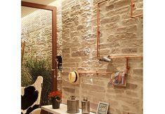 Os canos de cobre aparentes dão um ar industrial ao ambiente das arquitetas Denyse Santini e Águeda Santini. E o melhor: eles servem como cabideiros!