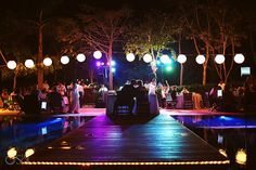 Destination wedding reception in Mexico at Grand Velas Riviera Maya. Lovely garden set-up, lights reflecting on the pool, color, vibrancy and a fabulous kiss! Mexico wedding photographers Del Sol Photography