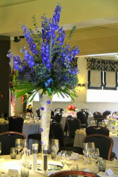 An explosion of Blue Hydrangeas and Baby Blue Eucalyptus with Hydrangeas, Eryngium and Orchids arranged on top of a tall elegant conical vase filled with Blue Delphinium jelly