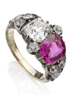 A 19th century pink sapphire and diamond ring Set with an old cushion-cut diamond and a cushion-cut pink sapphire with old round brilliant-cut diamond accents, all to pinched collet settings, between shoulders each set with a trefoil of old round brilliant-cut diamonds to a hoop with similarly-cut diamond accents, mounted in silver on gold.