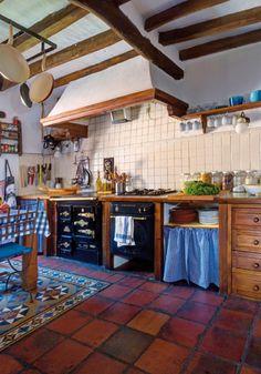a cocina de la vivienda principal, que cuenta con muchos elementos populares como el azulejo blanco artesanal, el suelo de barro y la propia cocina económica antigua.
