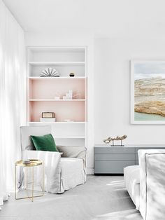 White living room with green pillow on armchair and two shelves on bookshelf painted pale pink