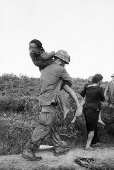 U.S. Marine carries a blindfolded woman suspected of Vietcong activities over his shoulder. She and other prisoners were rounded up during the joint Vietnamese-U.S. Operation Mallard, near Da Nang, Vietnam.: