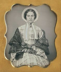 She's precious, and it seems to me she is trying hard not to laugh. Could it be that she is holding an avocado? There is an 1850s story here. I wish she could tell it. The broach she is wearing is a miniature portrait of a young woman.