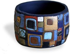 Tanya Mayorova's squares applied on a solid color bangle base continue our square theme. She takes a more painterly approach to her geometry, ...