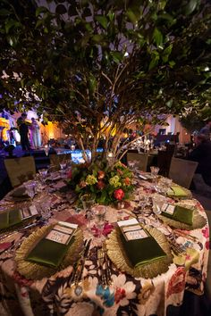 """Edge Floral Event Designers used a mix of grass, trees, candles, and green and pink flowers to create the Enchanted Forest ambience in the dining room."""