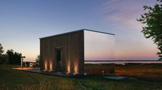 While three sides facing the view are mirrored, the entry side features natural timber.