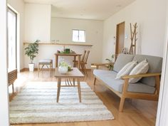 muji living room like: white, light, light wood, plants, nothing on walls, clean lines