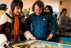 """Keith Moon playing pinball at the International Pinball Tournament, an event coinciding with the opening of the group's rock opera """"Tommy"""", ca. 1978."""