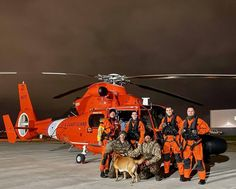 U.S. Coast Guard aircrew in front of their helicopter with the two hunters and a dog they rescued near Windsor, Ontario. The hunters were beset by weather in a 10-foot johnboat.
