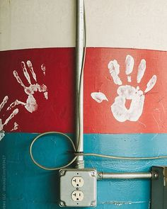 """One day these little hands will make the world a better place."" This #stockphoto is available via @stocksyunited search: #raymondforbesllc  #hand #handprints #fingerpaint #stripes #peace #pole #electric #outlet #industrial #redwhiteandblue"