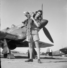 A trainee pilot shoulders his parachute harness in front of Hawker Hurricane Mark Is at No. 151 (Fighter) Operational Training Unit, Risalpur, India. (IWM)