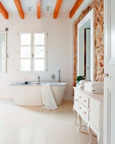 A toilet all white with stones in the wall.