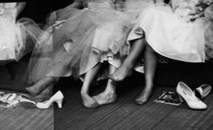 Teenage girls resting their feet during a formal dance at the Naval Armory