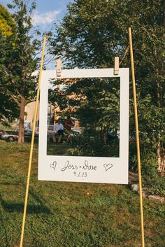 You can either set the two support poles in the ground, or put them in buckets filled with concrete (get a step-by-step in this how-to). Write your name and wedding date on the bottom of the photo frame, which you can make with poster board or foam board. Then, attach it to the poles with oversized clothespins, which you can find in most craft stores or online.Difficulty level: 💪💪