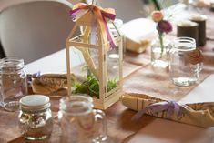 Barbecue wedding at Smokey Glen Farm: Floral burlap table runner with small bud vases filled with alstromeria, fern, baby's breath, and ranunculus. Mercury glass tea lanterns, tea votives, and real branch votives are scattered along the tables. Tan bandanna napkins tied with lavender, plum, ivory, or peach ribbons are at each place setting, along with guest favor mason jar mugs. Barbecue Wedding, Mason Jar Mugs, Burlap Table Runners, Baby's Breath, Ranunculus, Mercury Glass, Place Settings, Bud Vases, Fern
