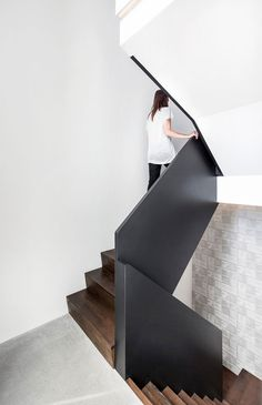 A clean and modern staircase.  The combination of black, wood and light grey give the staircase a warm feel.