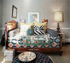 Bedroom Photo - Layered textiles on a wooden daybed against patterned wallpaper