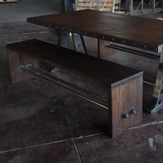 Hardwood bench with rod supports connected with large nuts and bolts.