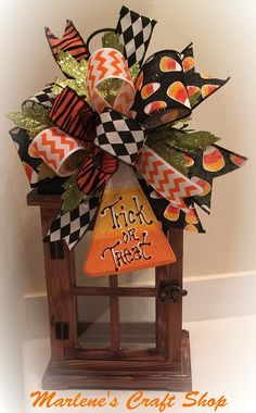 Halloween Lantern Swag/ Halloween accent bow with Candy corn ,Trick or Treat decoration. This cute Candy corn Lantern Swag is pictured on a 14 inchLantern. This Swag is ideal for lanterns between 10 - 18 inches. The bow features a mix of several fun Halloween ribbons. There are sparkly green leaves added as embellishments that make this Swag Sparkle! The main feature is a handcrafted wooden Candy corn ornament that reads trick or treat This Halloween bow would match most Halloween decor....