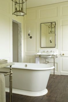 perpendicular tub placement, wood floor, paneled, jib door in Richmond House by Rose Uniacke