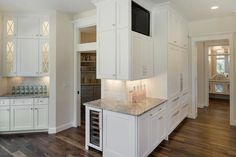 Angled kitchen features white shaker cabinets painted Benjamin Moore Simply White paired with Super White Granite countertops and a mini brick tile backsplash.