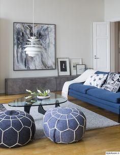 olohuone,sohva,taso,valaisin,tyynyt,sisustustyynyt,sohvapöytä,rahi,matto,moderni koti,lasipöytä,maalaus,harmaa,sininen,harmoninen,moderni