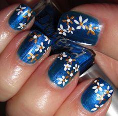 Sideswipe daisies on blue nail art