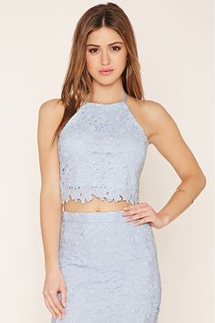 This knit cropped cami by WYLDR™ features a woven floral crochet overlay, adjustable straps that crisscross in back, a high neckline, a scalloped hem, and an exposed back zipper. Matching skirt available. Not available for in-store return.