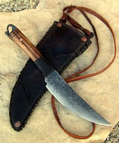 "Swept Tribal Necker by Rick.  tribal/skinner type blade… ""18th Century Tactical""  5160 Mat'l.  10 1/2″ overall.  5 1/2″ blade.  5″ handle (4 1/4″ scale/wrap length).  5/32″ spine at thickest.  Handle is distressed oak, rawhide wrap (epoxy sealed), copper pins, carved accent bands, finished with danish oil.  The neck sheath is 10oz cowhide covered in Goatskin."