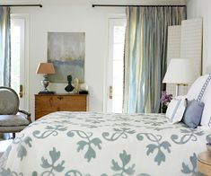 Artful Inspiration A gorgeous painting, which receives visual prominence between a pair of terrace doors, inspired the serene color palette and sumptuous silk textiles used to decorate this elegant master bedroom.