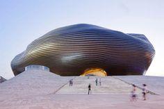 未来を感じずにはいられない特徴的なこの美術館は、モンゴル内奥の都市オルドスにある「オルドス美術館(Ordos Museum)」。ハイパー・アヴァンギャルドな若手建築家集団が設計を担当し、曲線がうねり、カプセル化された美術館となっている。