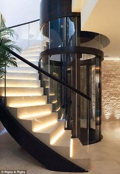 Nothing screams luxury like a spiral staircase wrapped around an elevator! Luxury home interior lift shaft made of bronze and glass runs through all four storeys of the home, hidden inside the spiral staircase Grand Staircase, Staircase Design, Luxury Staircase, Staircase Ideas, Modern Staircase, Modern House Design, Modern Interior Design, Loft Design, Interior Paint