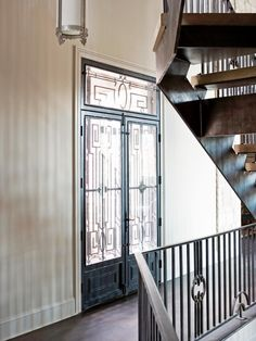 From the inside, the stunning details of this doorway's beautiful metal work are apparent. Walls are left bare to put the lovely design on full display.