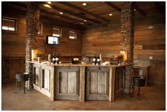 Here's a slightly different bar style for your with stone support beams and wood walls. Of course, it has a great looking rustic bar to go along with it too. Rustic Basement Bar, Basement Bar Plans, Basement Bar Designs, Modern Basement, Basement Kitchen, Basement Remodeling, Basement Ideas, Basement Bathroom, Basement Bars