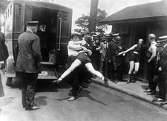 Women being arrested for wearing one piece bathing suits which reveal too much leg. Chicago, 1922