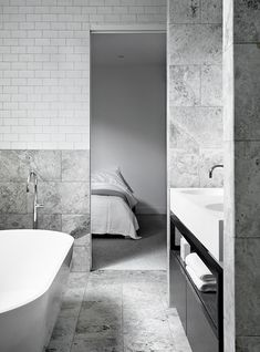 Grey and white bathroom/ensuite: marble tiles on walls and floor, white handmade subway wall tiles, white full-width countertop with integrated his-and-her basins, black wood and metal vanity underframe with cabinet/drawer storage and open shelf for towels, freestanding bathtub with chrome mixer tap, light grey carpet in bedroom, white and grey bed linen