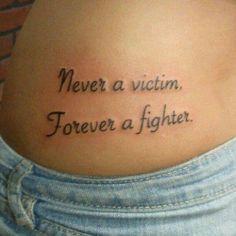 "Little hip tattoo saying ""Never a victim. Forever a fighter."" ""Nunca una víctima. Siempre un luchador."""