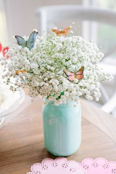Simplest Easter / spring centerpiece ever! Fill a mason jar with a bunch of baby's breath and top with butterfly stickers from Martha Stewart